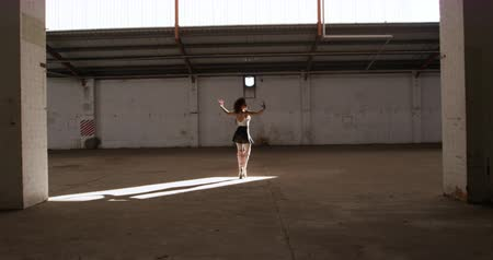 vocação : Side view of a mixed race female ballet dancer practicing in an empty warehouse, dancing and turning on tiptoes, slow motion