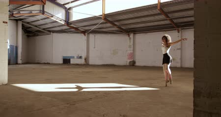 vocação : Side view of a mixed race female ballet dancer practicing in an empty warehouse, standing on tiptoes and jumping, slow motion