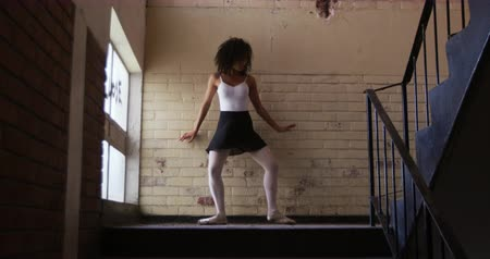 baletnica : Low angle front view of a mixed race female ballet dancer practicing in an empty warehouse, dancing and leaning on a brick wall by a staircase, slow motion Wideo