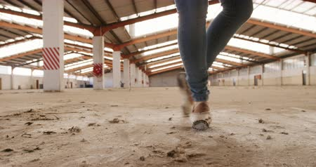 fegyelem : Close up of legs of a female ballet dancer practicing in an empty warehouse, dancing and turning around, slow motion
