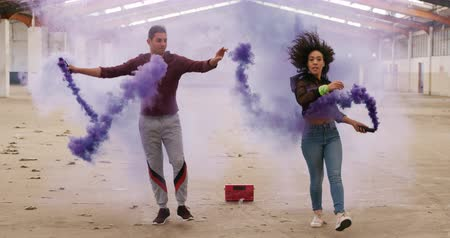 grenade : Front view of mixed race female and Caucasian male dancers practicing in an empty warehouse together, holding smoke grenades, dancing and jumping, slow motion Stock Footage