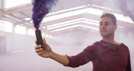 friendship dance : Front view of Caucasian male and mixed race female dancers in an empty warehouse, standing and holding smoke grenades, slow motion