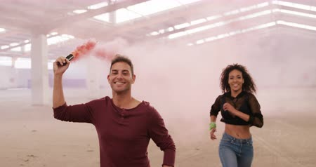 grenade : Front view of mixed race female and Caucasian male dancers in an empty warehouse, running and smiling, man holding smoke grenade, slow motion