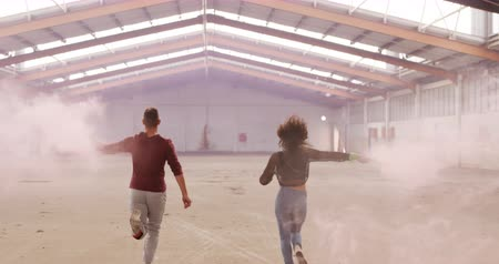 grenade : Rear view of mixed race female and Caucasian male dancers in an empty warehouse, running and holding smoke grenades, slow motion
