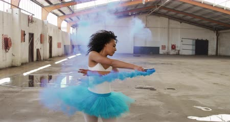 grenade : Front view of mixed race female dancer practicing in an empty warehouse, running, jumping and holding smoke grenade, slow motion Stock Footage