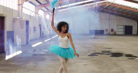 grenade : Side view of mixed race female dancer practicing in an empty warehouse, dancing, turning around and holding smoke grenade, slow motion Stock Footage