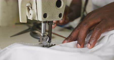 üreten : Front view close up of hands of an African male tailor in a township workshop, using a sewing machine, slow motion Stok Video