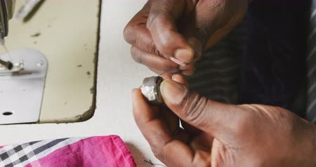 spool : Side view close up of hands of an African male tailor in a township workshop, using a sewing machine and putting thread on spool, slow motion Stock Footage