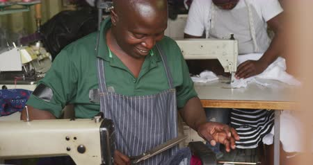 vocação : Front view of two African male tailors in a township workshop, sitting by sewing machines, holding fabric, cutting and sewing, slow motion