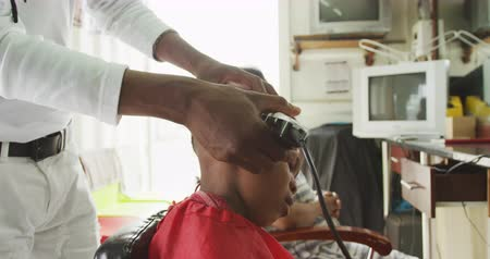 vocação : Side view mid section of an African male hairdresser with dreadlocks in a township hair salon, shaving head of an African boy, slow motion