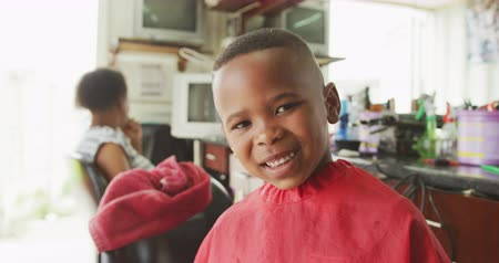 cape town : Portrait of a happy African boy in a township hair salon, looking at camera after a haircut, his mum waiting in the background, slow motion Stock Footage
