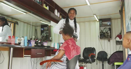 suszarka : Front view of an African male hairdresser in a township hair salon, drying hair of his African female client, slow motion