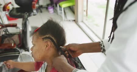 braid hairs : High angle side view of an African male hairdresser in a township hair salon, plaiting hair and doing hair extensions for an African female client, slow motion