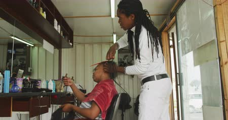 braid hairs : Side view of an African male hairdresser in a township hair salon, adding hair extensions for an African female client, slow motion Stock Footage