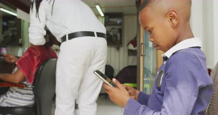 パーラー : Side view of an African boy in a township hair salon using a tablet computer, male African hairdresser with dreadlocks doing hair extensions for his African female client in the background, slow motio