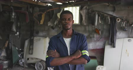crossed : Portrait of a happy African male panel beater in a township workshop, looking at camera with arms crossed, slow motion Stock Footage