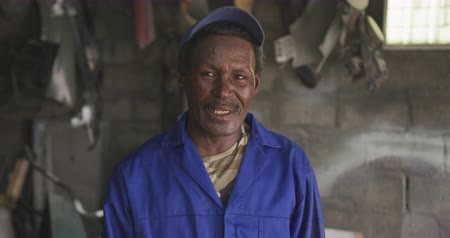 trabalhador manual : Portrait of a happy senior African male panel beater in a township workshop, wearing a cap, looking at camera and smiling, slow motion