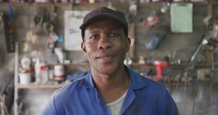 garagem : Portrait of a happy African male panel beater in a township workshop, wearing a cap, looking at camera smiling, slow motion