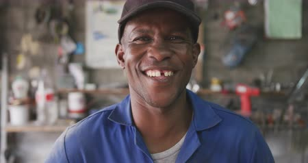 мастер на все руки : Portrait of a happy African male panel beater in a township workshop, wearing a cap, looking at camera and smiling, slow motion Стоковые видеозаписи