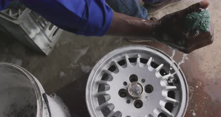 tartomány : High angle side view of an African male panel beater in a township workshop, cleaning an alloy wheel, slow motion