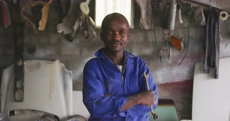 trabalhador manual : Portrait of a happy African male panel beater in a township workshop, holding a wrench, looking at camera and smiling, slow motion Vídeos
