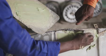cape town : Front view of hands of an African male owner of a panel beater workshop in a township, standing next to his employee painting a car part, giving instructions, slow motion Stock Footage