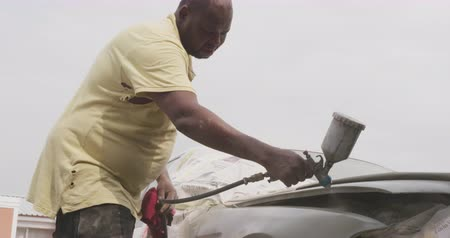 bricoleur : Low angle side view of an African male panel beater in a township workshop, using a spraying gun to paint a car, slow motion