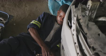 trabalhador manual : High angle front view of an African male car mechanic in a township workshop, lying next to car and toolbox, repairing the car, slow motion