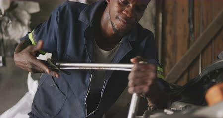 cape town : Front view of an African male car mechanic in a township workshop, repairing a car with a car boot open Stock Footage