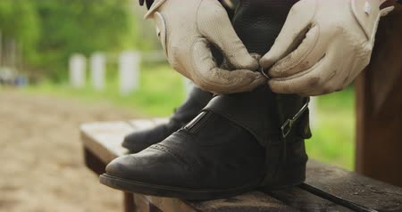 spona : Low section side view of a smartly dressed male equestrian wearing gloves, with his feet up on a bench, adjusting the spurs on his riding Dressage boots before horse riding, slow motion Dostupné videozáznamy