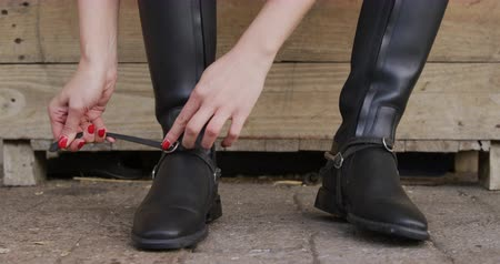 fegyelem : Dressage jockey getting ready. Front view close up of a Caucasian woman sitting and putting spurs on her riding boots at a stable before horse riding, slow motion