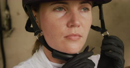 tutturma : Dressage jockey getting ready. Portrait close up of a Caucasian woman fastening her riding hat in a stable, with a horse in the background, slow motion Stok Video