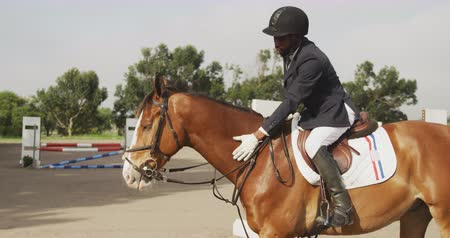 terbiye : Side view of a smartly dressed African American man wearing a riding hat riding a chestnut Dressage horse in a paddock and stroking its neck, slow motion