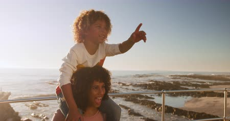 promenáda : Front view of mixed race woman with her son enjoying family time by the seaside together on a sunny day with blue sky, mother carrying her son on her shoulders, slow motion Dostupné videozáznamy