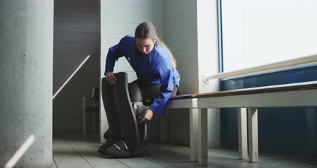 keeper : Side view of a teenage Caucasian female hockey player sitting in the changing room securing her leg guards before playing field hockey, slow motion Stock Footage