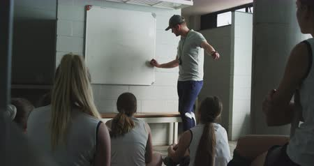 focussed : Side view of a Caucasian male hockey coach standing, talking to a team of Caucasian teenage female hockey players and drawing a game plan on a whiteboard in the changing room before a hockey game, slow motion Stock Footage