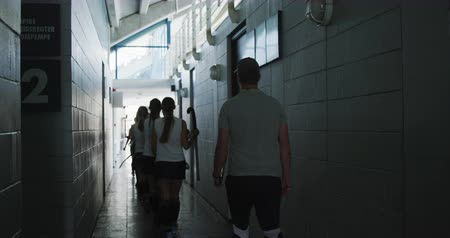прихожая : Rear view of a Caucasian male hockey coach and a team of Caucasian teenage female hockey players in a team uniform leaving the changing room and walking in a corridor before a hockey game, slow motion