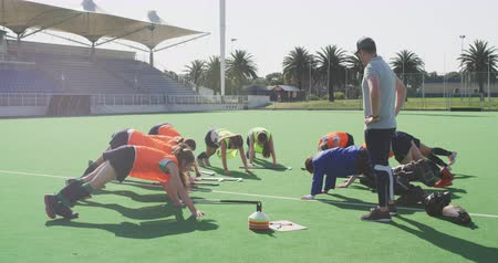 antrenör : Side view of a Caucasian male hockey coach standing and watching a team of teenage Caucasian female hockey players on all fours, exercising and stretching on the pitch before playing hockey, slow motion Stok Video