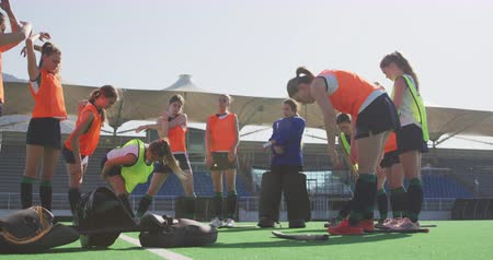 veldhockey : Side view of a team of Caucasian teenage female hockey players stretching on the pitch before playing hockey, slow motion Stockvideo