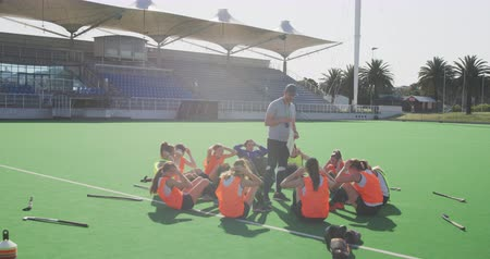 veldhockey : Front view of a Caucasian male hockey coach standing and watching a team of Caucasian teenage female hockey players doing sit ups, exercising on the pitch before playing hockey, slow motion