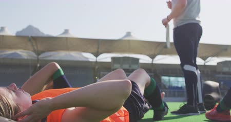 amontoado : Low section side view of a Caucasian male hockey coach standing and watching a team of Caucasian teenage female hockey players doing sit ups, exercising on the pitch before playing hockey, slow motion Stock Footage