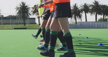 ajoelhado : Low section side view of a team of Caucasian teenage female hockey players in a row, holding hockey sticks on the pitch, kneeling, stretching and warming up before playing hockey, slow motion
