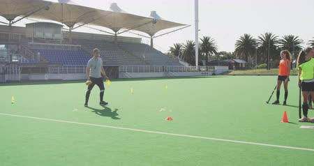 amontoado : Front view of a Caucasian male hockey coach instructing a team of Caucasian teenage female hockey players, warming up on the pitch before playing hockey, slow motion