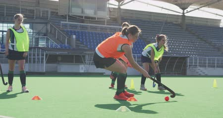 hokej : Side view close up of a teenage Caucasian female hockey player training on the pitch with hockey stick and ball, while her teammates train in the background, slow motion