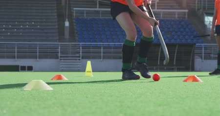 amontoado : Low section front view of a teenage Caucasian female hockey player training on the pitch with hockey stick and ball, while her teammates train in the background, slow motion Stock Footage