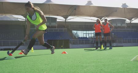 hokej : Side view close up of a teenage Caucasian female hockey player training on the pitch with hockey stick and ball, while her teammates and Caucasian male coach watch in the background, slow motion