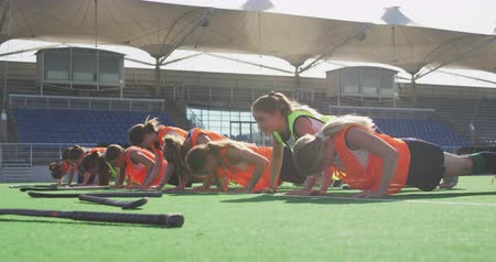 hokej : Side view of a teenage Caucasian female hockey team training on the pitch, doing press ups in a line, with their hockey sticks on the ground in front of them, slow motion