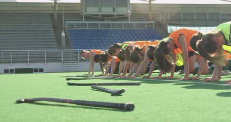 hokej : Side view of a Caucasian male coach instructing a teenage Caucasian female hockey team training on the pitch, doing exercises in a line, with their hockey sticks on the ground in front of them, backlit by sunlight, slow motion
