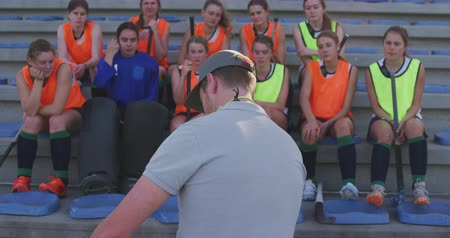focussed : Rear view of a Caucasian male coach standing and instructing a teenage Caucasian female hockey team, sitting on stadium seats at a sports field, slow motion