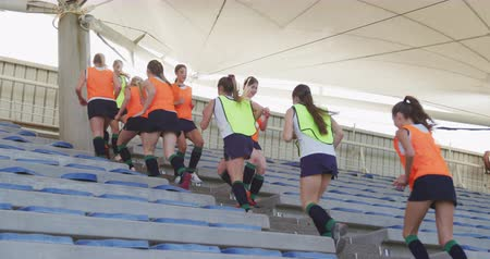 focussed : Side view of a teenage Caucasian female hockey team running up and down steps between stadium seats at a sports field, warming up before playing on the hockey pitch, slow motion